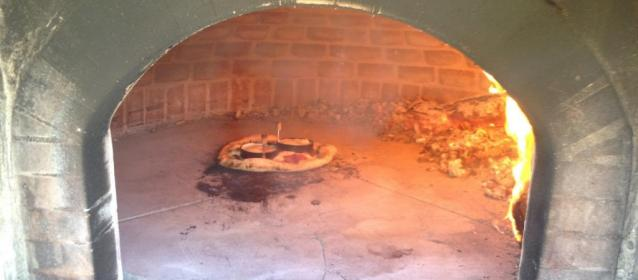 This black oven is a traditional wood burning pizza oven.